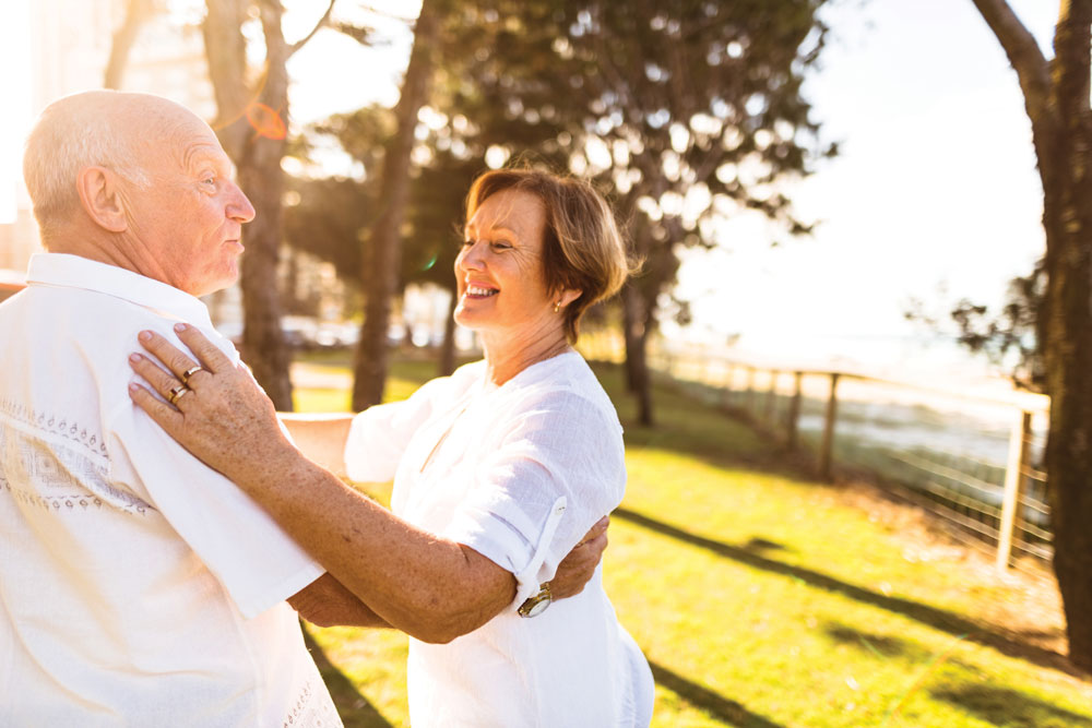 Charter Senior Living of Franklin Residents couple dressed all in white smiles and dances together outdoors