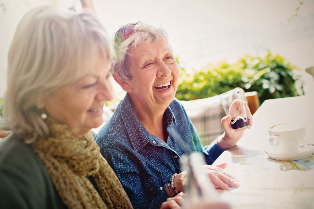 Two female residents of Charter Senior Living of Franklin smile and share beverages while sitting at an outdoor table